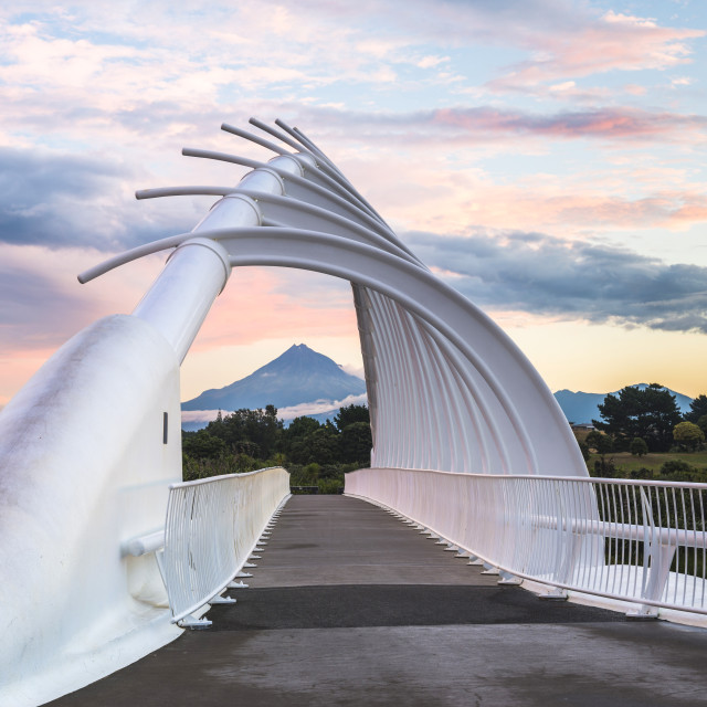 """Te Rewa Rewa Bridge at sunset with Mount Taranaki (Mount Egmont) behind,..."" stock image"