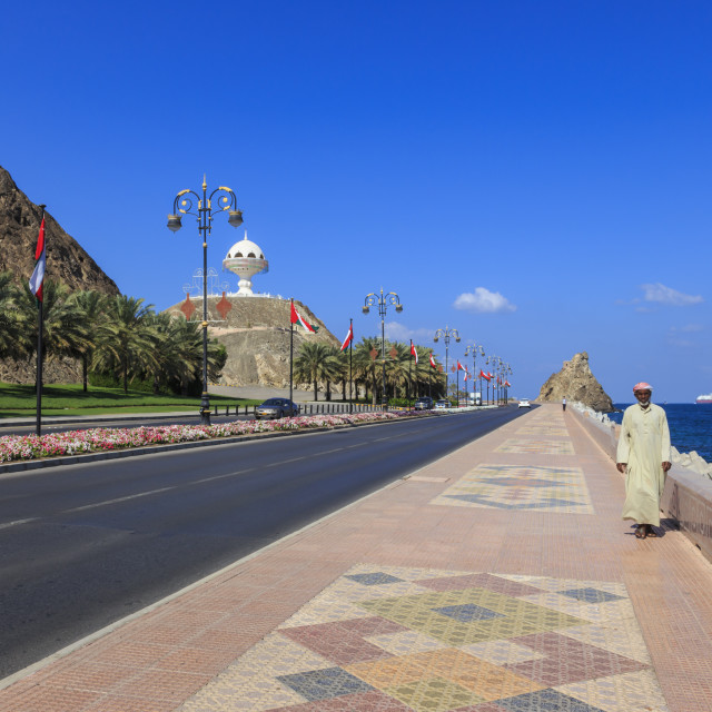 """Man wearing dishdasha walks along Mutrah Corniche with national flags, flower..."" stock image"