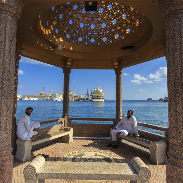 """Seated Omani men wearing traditional dishdasha on Mutrah Corniche, with view..."" stock image"