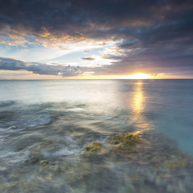 """""""The lights of sunset are reflected in the blue sea, Hawksbill Bay, Antigua,..."""" stock image"""