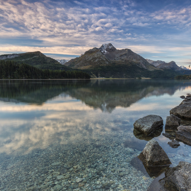 """Pink sky at dawn illuminates the peaks reflected in Lake Sils Engadine Canton..."" stock image"