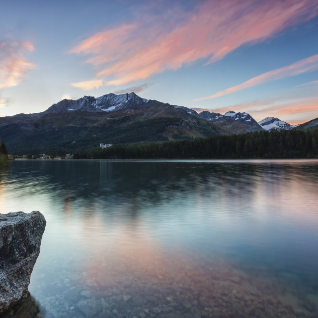 """Pink sky at dawn illuminates the peaks reflected in Lake Sils, Engadine,..."" stock image"