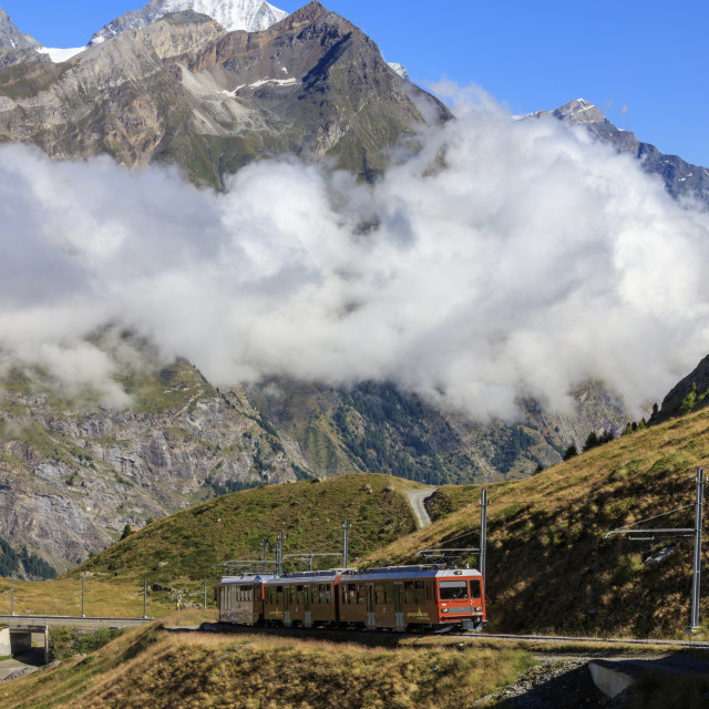 """The red Bahn train proceeds with the peak of Dent Herens in the background..."" stock image"