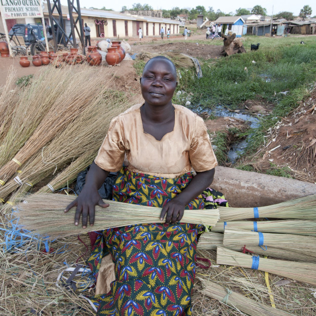 """""""Lira - work - woman selling home-made brushes by the side of the road"""" stock image"""
