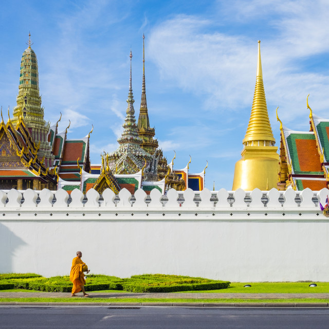 """""""A monk passes in front of Wat Phra Kaew and the Grand Palace, Bangkok, Thailand"""" stock image"""