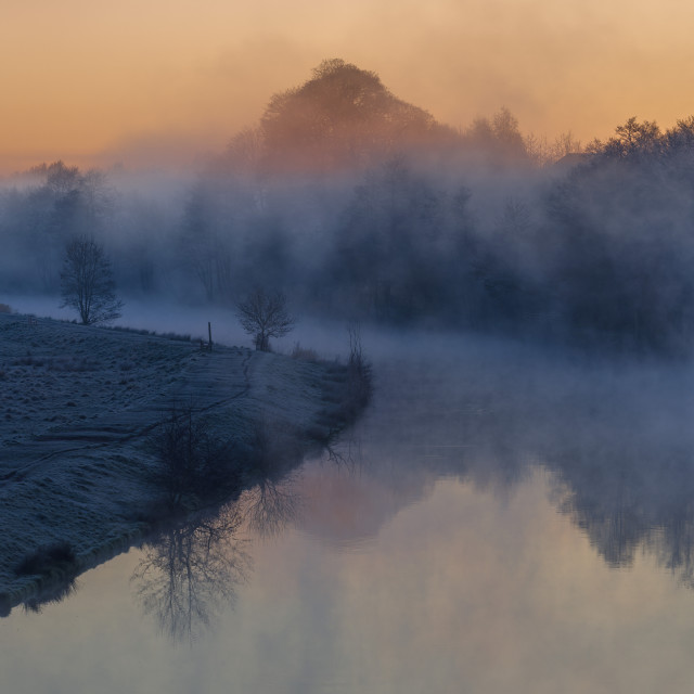 """Winter dawn along the River Weaver with mist lingering among the trees and..."" stock image"