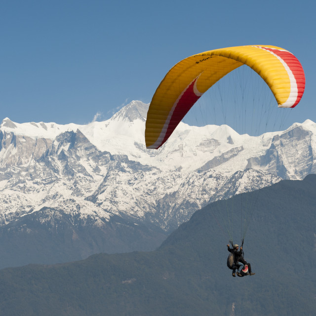 """A tandem paraglider flys above Pokhara with views of the Annapurnas in Nepal"" stock image"