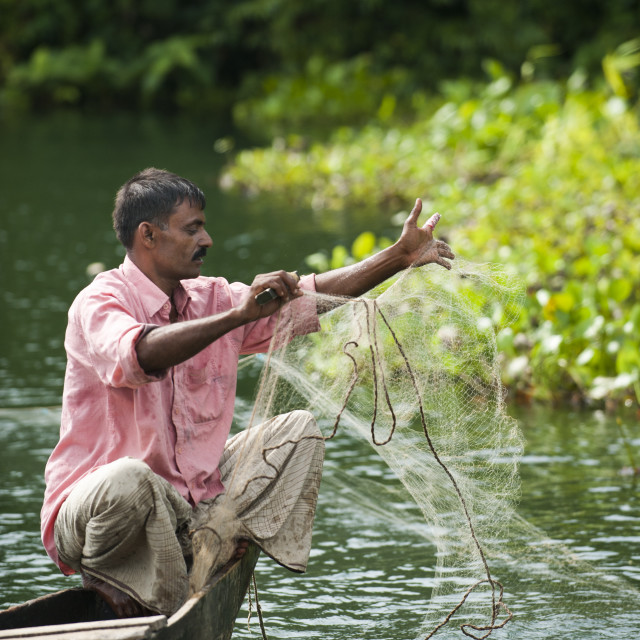 """""""A man pulls in his fishing net on Kaptai lake in the Chittagong Hill Tracts..."""" stock image"""