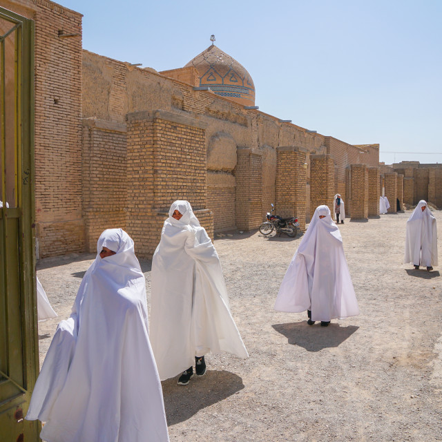 """Women in white chadors leaving Jameh Mosque, Varzaneh, Iran"" stock image"