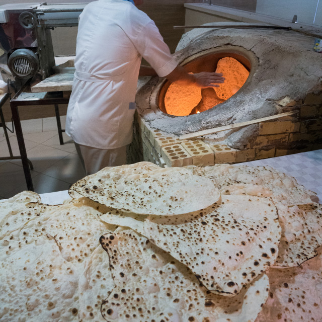 """Traditional baker at work at his oven, Ramsar, Iran"" stock image"