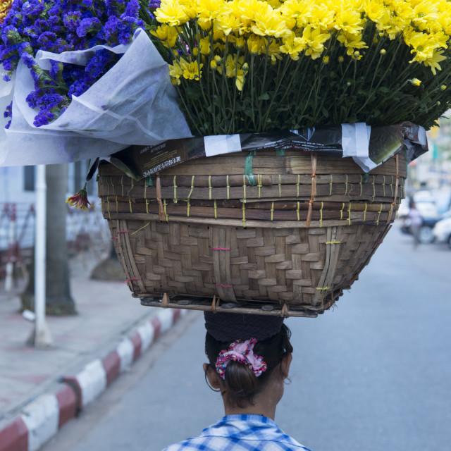 """Woman carrying large flower basket on her head. Yangon. Myanmar (Burma)."" stock image"