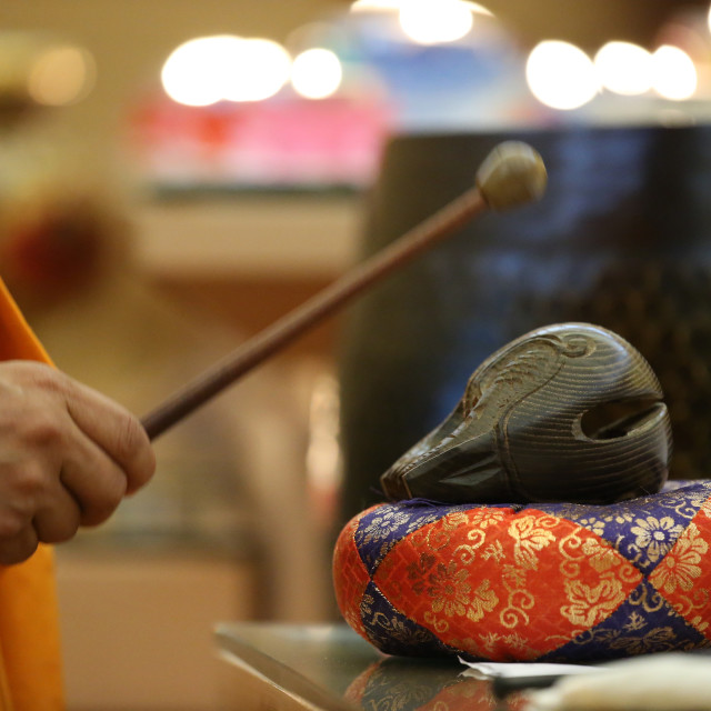 """""""Fo Guang Shan temple. Monk playing on a wooden fish (percussion instrument)."""" stock image"""