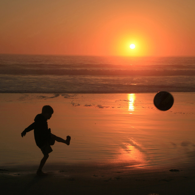 """A child playing soccer at Clifton Beach, in Cape Town, South Africa. July 17,..."" stock image"