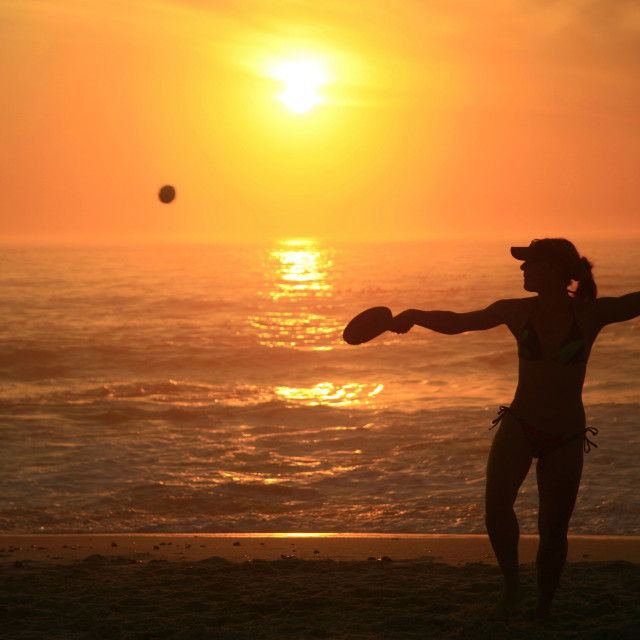 """A woman playing beach bats on Clifton Beach, in Cape Town, South Africa...."" stock image"