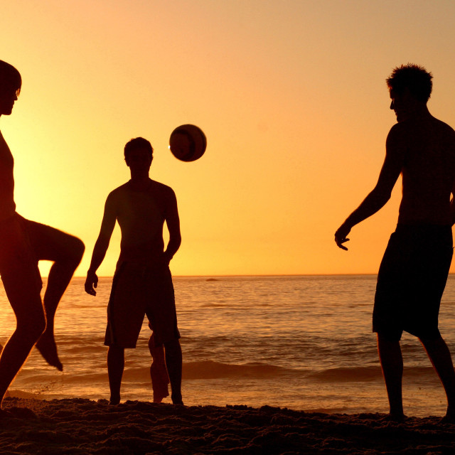 """Playing football on Clifton Beach, Cape Town, South Africa. February 9, 2005."" stock image"