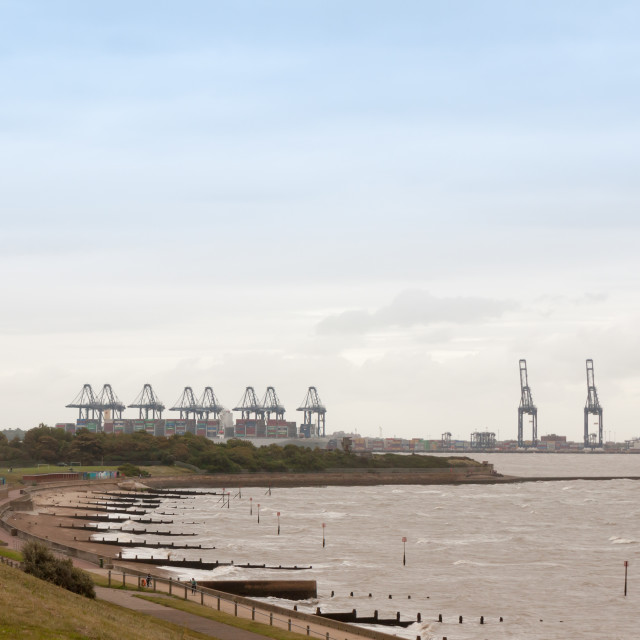 """""""sea industry cargo and shipping cranes in the distance beach groynes Harwich..."""" stock image"""