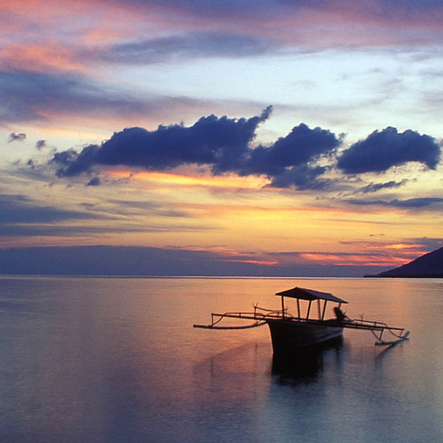 """""""sunset over Manado Tua Volcano with boat on water, Sulawesi. Spice Islands,..."""" stock image"""