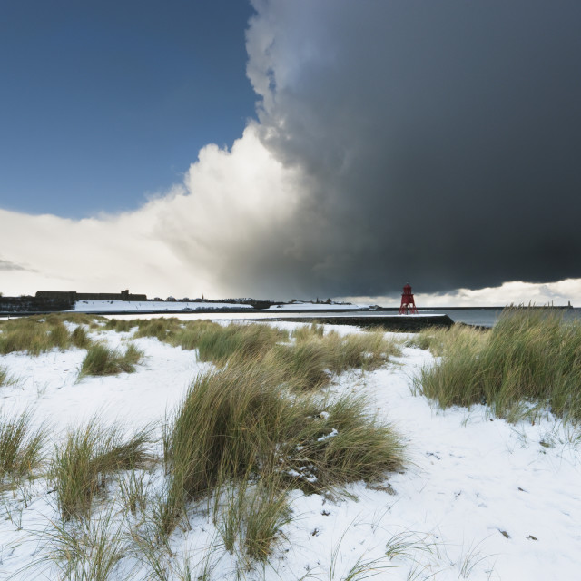 """Dark Clouds And Blue Sky Over A Red Lighthouse Along The Coast In The Winter;..."" stock image"