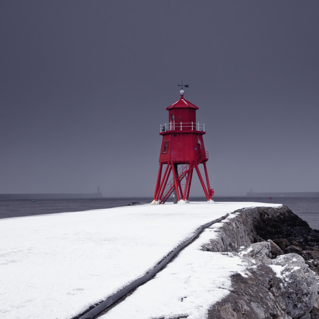 """A Red Lighthouse Under A Stormy Sky Along The Coast In Winter; South Shields,..."" stock image"
