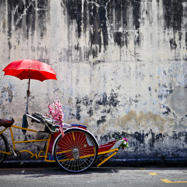 """""""A Traditional Penang Trishaw Sits In Front Of An Old Weathered Wall; Penang..."""" stock image"""