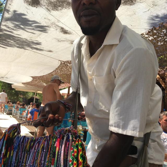 """""""Man selling bracelets on beach in Greece"""" stock image"""