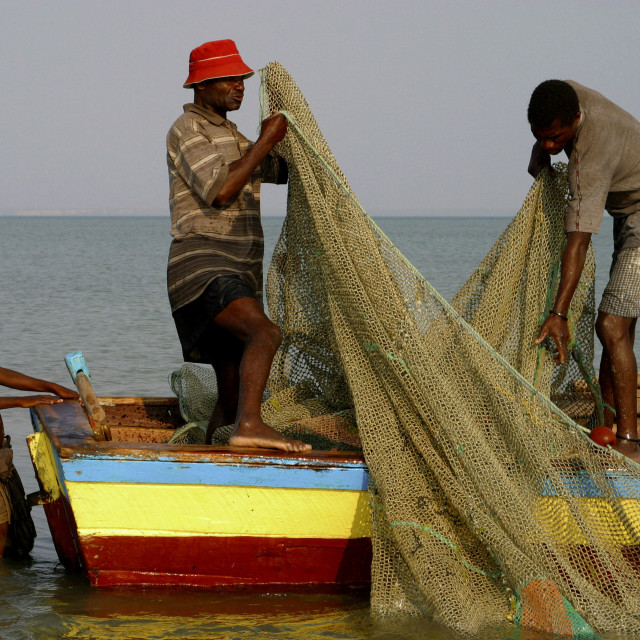 """Fishermen on boat preparing their nets, Benguerra Island, Bazaruto..."" stock image"