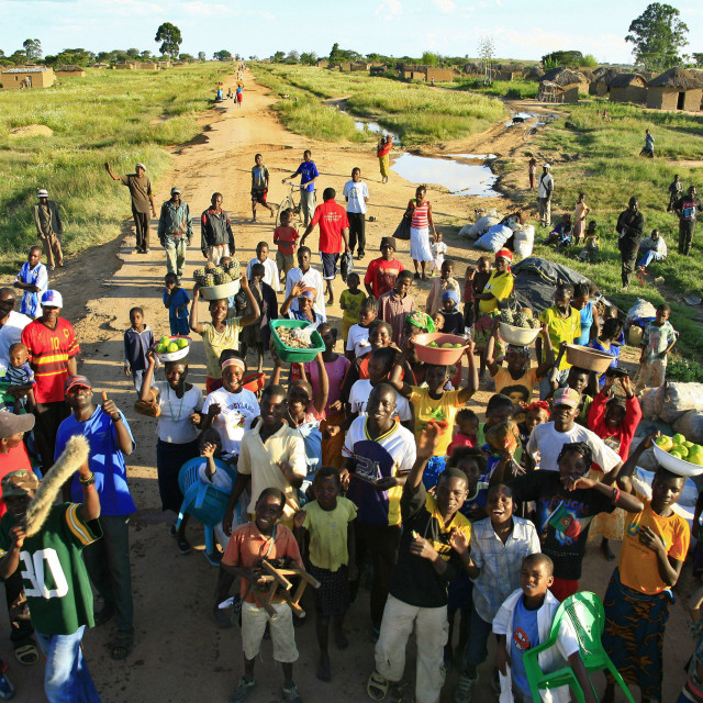 """""""A group of people smile and wave in the village of Caconda, Angola. April 10,..."""" stock image"""