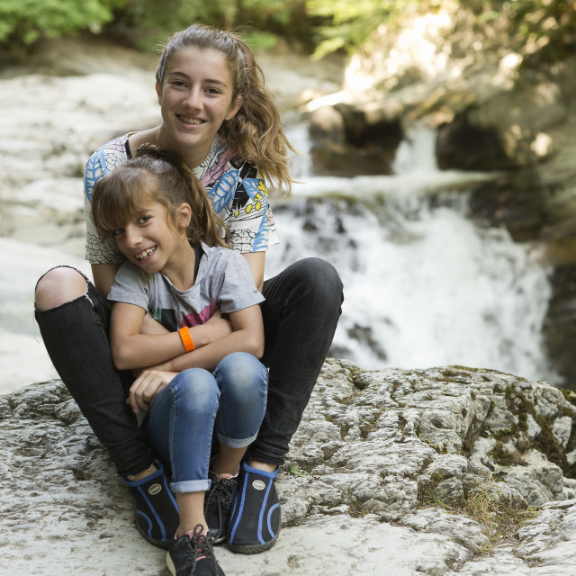 """""""Sisters sitting on rocks next to a river."""" stock image"""
