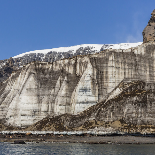 """""""Rust-colored volcanic tuff cliffs above a dark material filled glacier at..."""" stock image"""