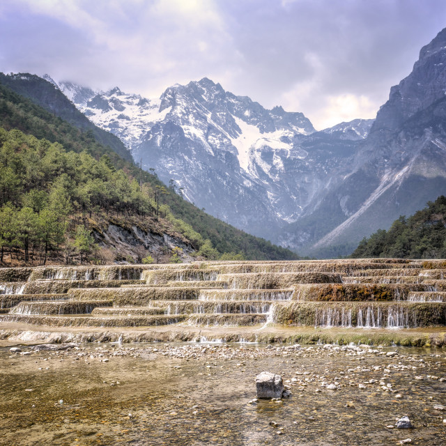 """Cascading falls at Baishuihe with Jade Dragon Snow Mountain backdrop,..."" stock image"