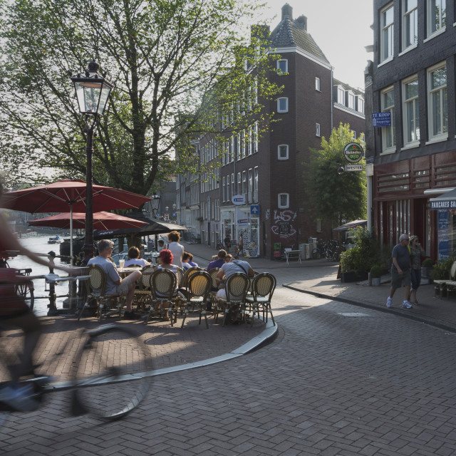 """Cyclist and pavement cafe, Amsterdam, The Netherlands, Europe"" stock image"