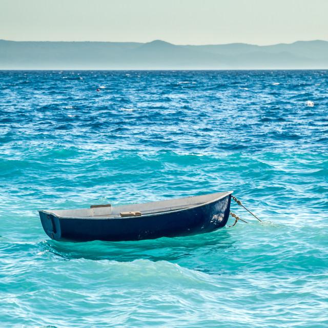 """little blue boat is seesawing on waves in mediterrean"" stock image"