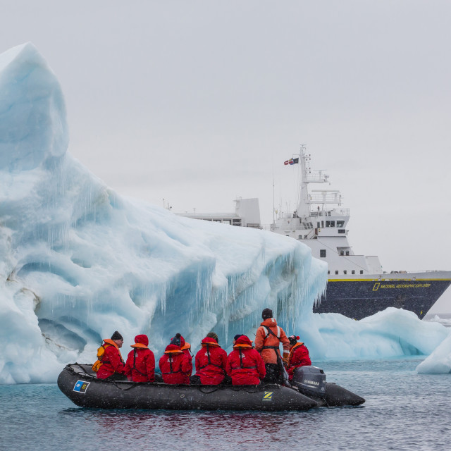 """""""Lindblad Expeditions guests in a Zodiac approach a glacial iceberg at Brown..."""" stock image"""
