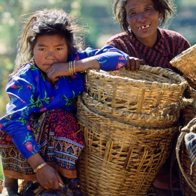 """A mother & daughter awaiting a bus to take them to the local market , Nepal"" stock image"