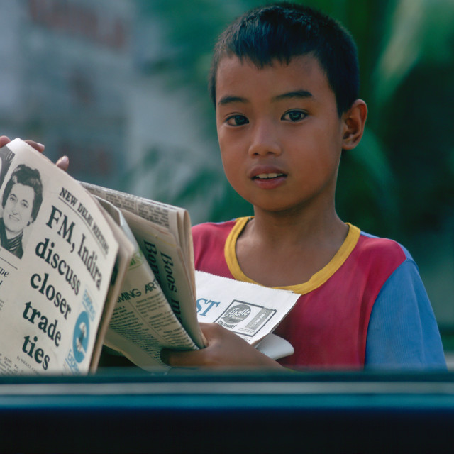 """""""Boy sells newspapers at car windows in Manila, Philippines"""" stock image"""