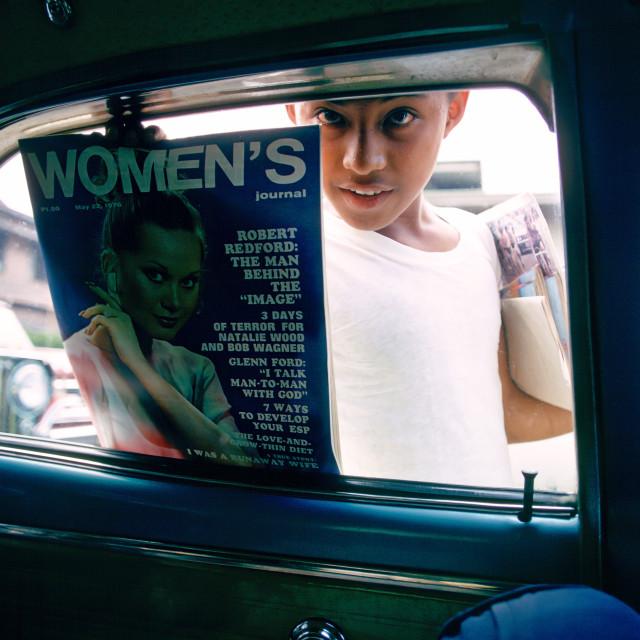 """Boy sells magazines at car windows in Manila, Philippines"" stock image"