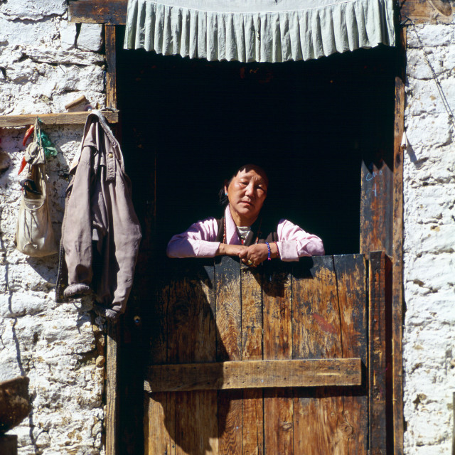 """Woman at doorway of house, Paro, Bhutan"" stock image"