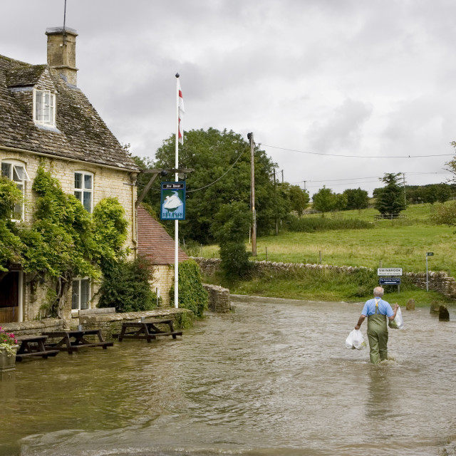 """Man wades through flood water in Swinbrook, Oxfordshire, England, United Kingdom"" stock image"