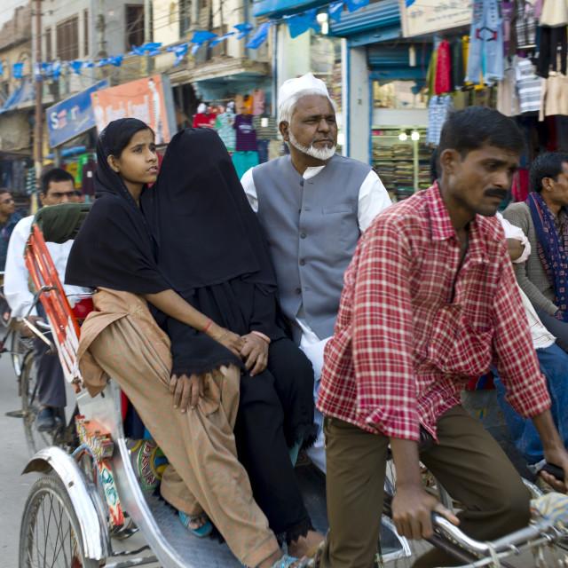 """""""Street scene in holy city of Varanasi, muslim family ride in rickshaw,..."""" stock image"""