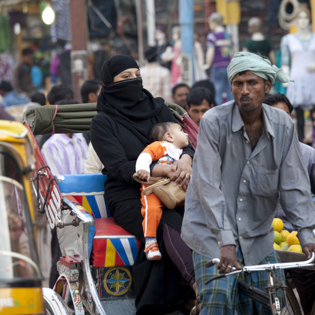 """Muslim woman and child travel by rickshaw in crowded street scene in city of..."" stock image"