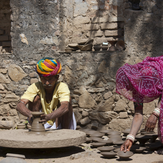"""""""Indian potter in traditional Rajasthani turban works at home with his wife..."""" stock image"""