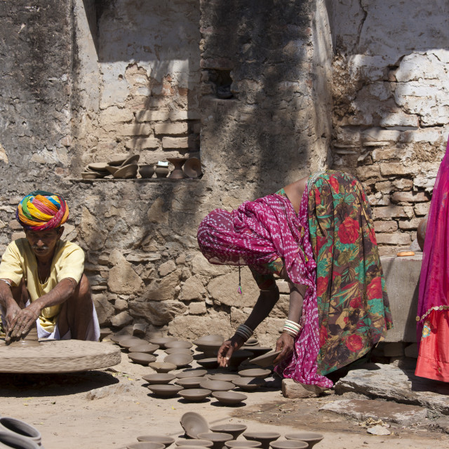 """""""Indian potter in traditional Rajasthani turban works at home with his family..."""" stock image"""