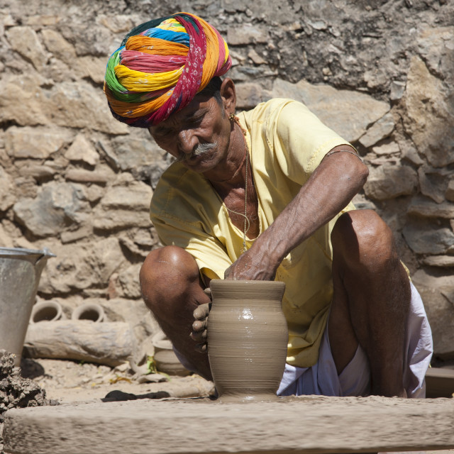 """""""Indian potter in traditional Rajasthani turban works on potter's wheel at..."""" stock image"""