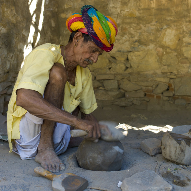 """""""Indian potter in traditional Rajasthani turban works at home preparing clay..."""" stock image"""
