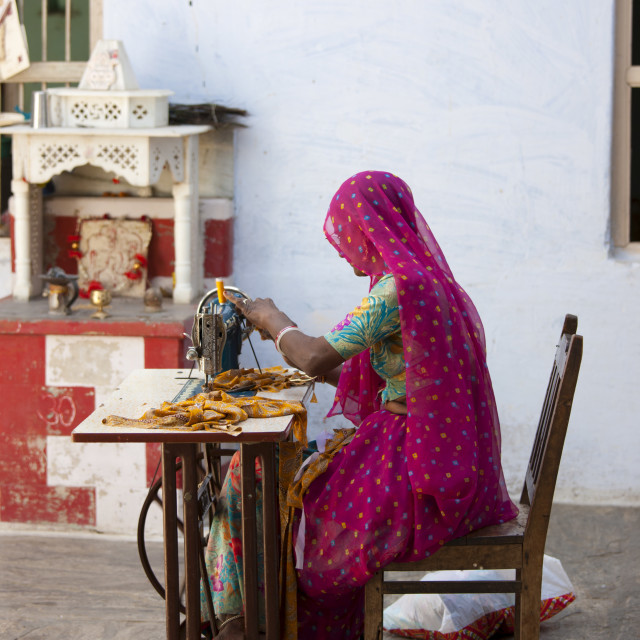 """Indian woman wearing traditional Rajasthani sari works at home using sewing..."" stock image"