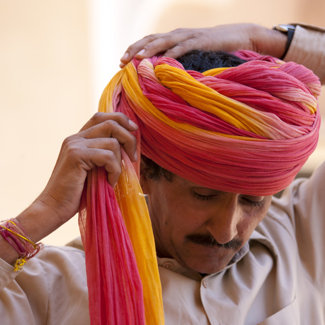 """Hindu ceremonial guard putting on Rajasthani turban at Mehrangarh Fort at..."" stock image"