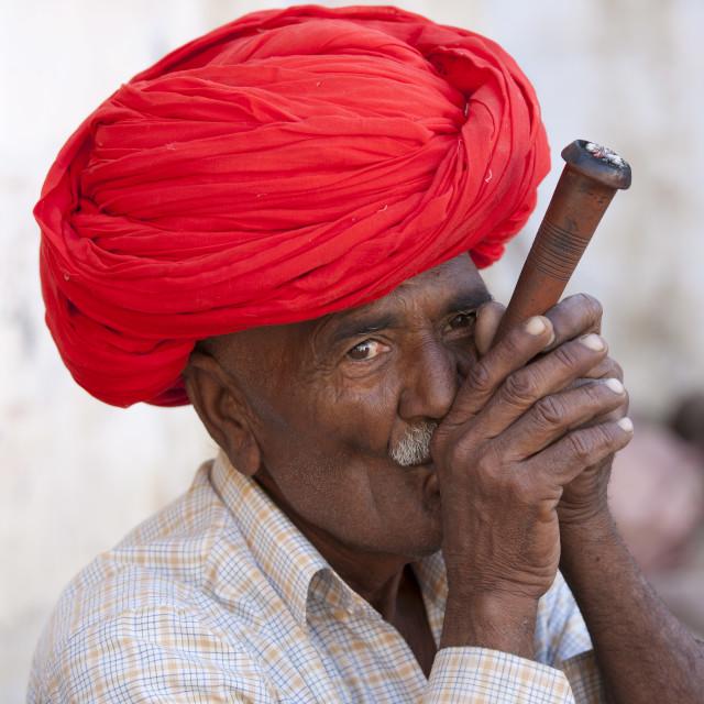 """Indian man wearing Rajasthani turban smokes traditional clay pipe in Narlai..."" stock image"