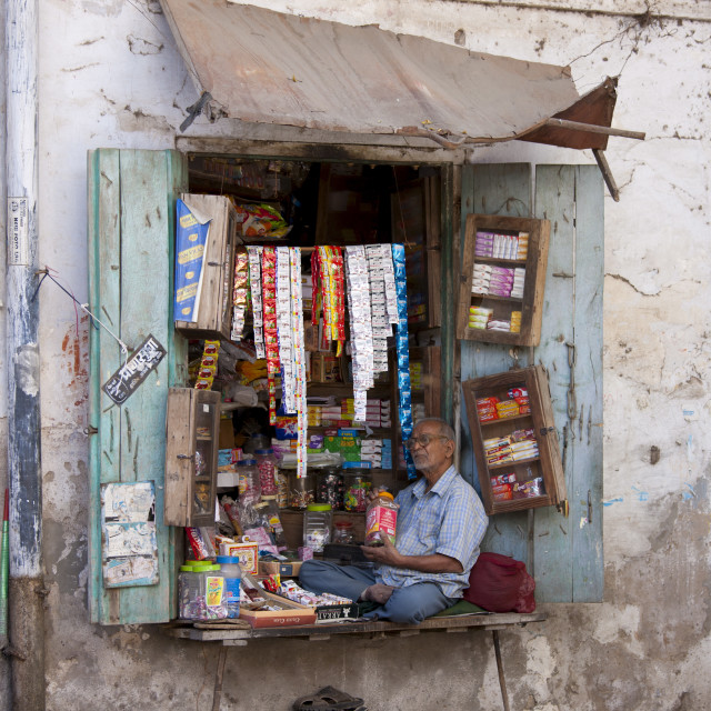 """""""Stallholder selling sweets, tobacco and foods sits in shop window in old town..."""" stock image"""