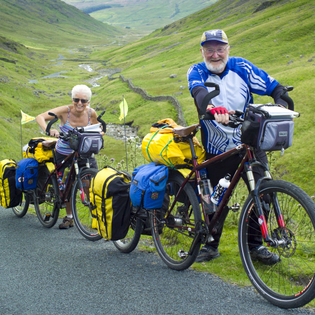 """""""Cyclists on roadway through Wrynose Pass in the Dudden Valley part of the..."""" stock image"""