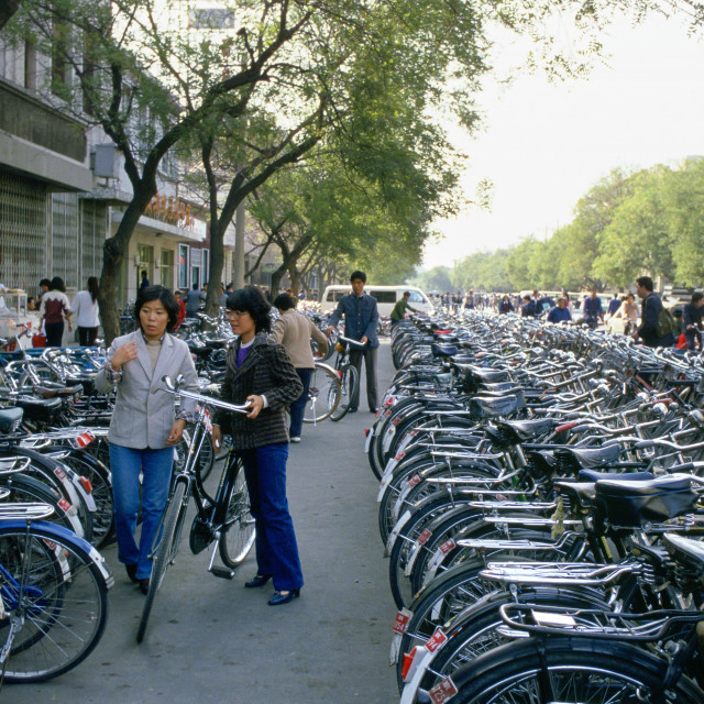 """Young women parking bicycle in crowded bicycle park, Beijing, China"" stock image"